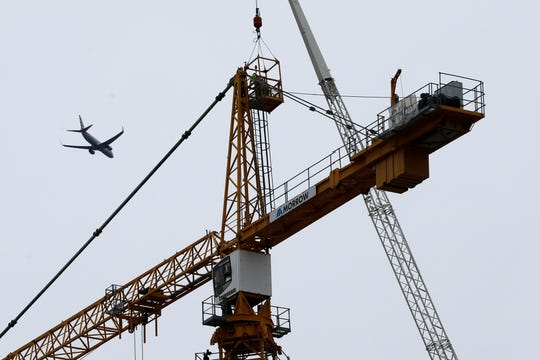 Workers in a bucket begin the process of planting explosive charges on two unstable cranes at the Hard Rock Hotel, which underwent a partial, major collapse on Saturday, Oct. 12, in New Orleans, viewed Thursday, Oct. 17, 2019. Authorities say explosives will be strategically placed on the two unstable construction cranes in hopes of bringing them down with a series of small controlled blasts ahead of approaching tropical weather. Officials hope to bring the towers down Friday without damaging nearby businesses and historic buildings in and around the nearby French Quarter. (AP Photo/Gerald Herbert)