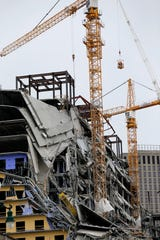 Workers in a bucket hoisted by a crane begin the process of preparing the two unstable cranes for implosion at the collapse site of the Hard Rock Hotel, which underwent a partial, major collapse while under construction Oct., 12, in New Orleans.