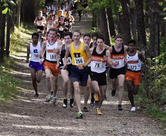 Hartland's Riley Hough (256), and Brighton's Zach Stewart (78) and Scott Spaanstra (76) run up front in the first mile of the KLAA cross country meet at Huron Meadows Metropark on Thursday, Oct. 17, 2019.