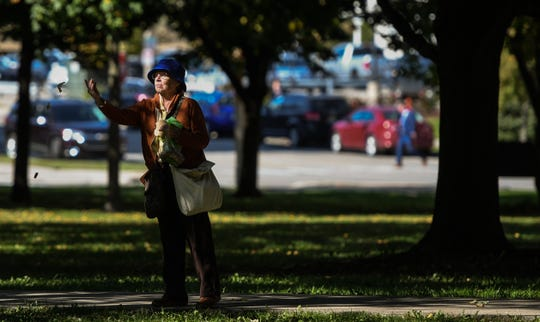 A woman feeds squirrels Wednesday, Oct. 9, 2019, at Reutter Park in downtown Lansing.