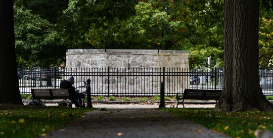 A man naps on a bench in Reutter Park in downtown Lansing on Oct. 17, 2019.