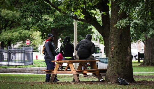 People chat around a picnic table at Reutter Park, Friday, Oct. 4, 2019.  This past summer, the organization Punks with Lunch placed four picnic tables in the park and chained them to a table.  City officials and the organization have since been at odds about the tables in the city-owned public park and want them removed by fall.