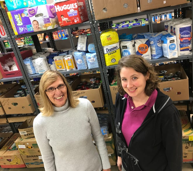 Sharon Draeger (left), a volunteer at the St. Vincent de Paul Outreach Food Pantry, and Stacy Clements, the pantry's manager, stand in an aisle containing food and other household necessities.