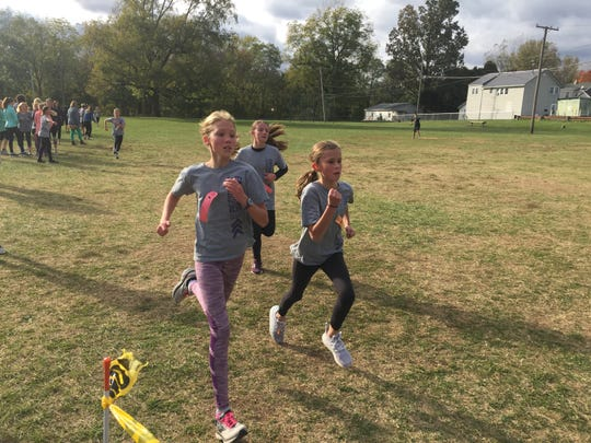 Three girls in the running club at Eastern Elementary School in Lexington head for the finish line of a 1-mile run.