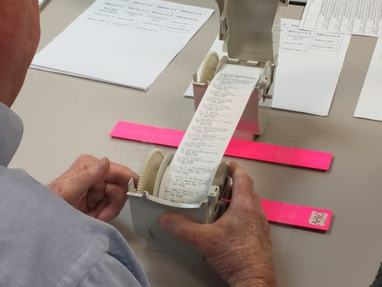 Election workers count the votes in December in the 2018 Marion County prosecutor's race by viewing individual votes on the paper record produced by the electronic voting machines.