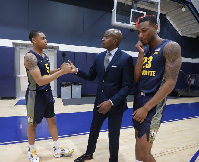 Marquette guard Greg Elliott and Marquette Golden Eagles forward Jamal Cain talk with assistant coach Dwayne Killings.