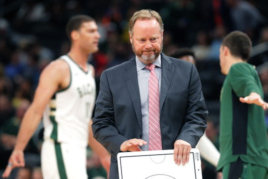 Bucks coach Mike Budenholzer grabs his white board to diagram a play during a timeout against the Timberwolves.