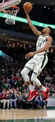 Bucks forward Giannis Antetokounmpo saves his breakaway dunks for the regular season as he opts for a lay up against the Timberwolves during the first half.