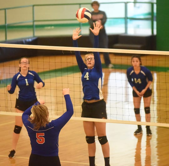 Cotter's Morgan Zick attempts a block as teammates Adalynn Clonts and Destiny Parker prepare to move in.