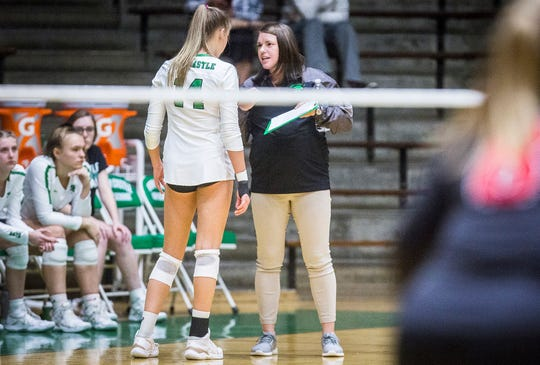 New Castle volleyball coach Sarah Roush talks to junior Nicole Wilkinson as the Trojans face off against Richmond at New Castle High School Thursday Oct. 17, 2019.