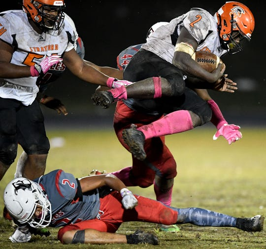 Stratford's James Moore (2) leaps over East Nashville's Rashaun Richardson (2) during the second half at East Nashville High School in Nashville, Tenn., Thursday, Oct. 17, 2019.
