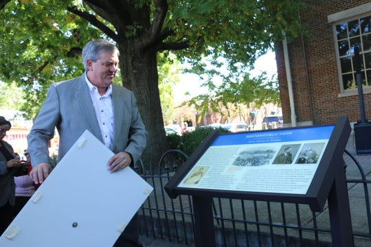 Pastor Kevin Riggs unveils a marker about Reconstruction in front of the historic courthouse in Franklin on Oct. 17, 2019.