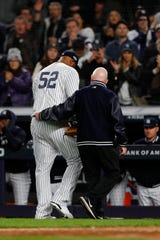 Oct 17, 2019; Bronx, NY, USA; New York Yankees pitcher CC Sabathia (52) is walked off the field by a member of the training staff after suffering an apparent injury against the Houston Astros during the eighth inning of game four of the 2019 ALCS playoff baseball series at Yankee Stadium. Mandatory Credit: Noah K. Murray-USA TODAY Sports