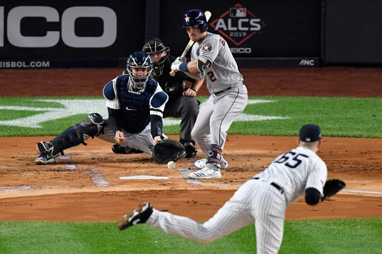 Oct 18, 2019; Bronx, NY, USA; New York Yankees starting pitcher James Paxton (65) throws a wild pitch to catcher Gary Sanchez (24) against Houston Astros third baseman Alex Bregman (2) during the first inning of game five in the 2019 ALCS playoff baseball series at Yankee Stadium. Houston Astros center fielder George Springer (not pictured) scored on the play.