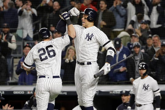 New York Yankees'DJ LeMahieu (26) celebrates with Aaron Judge after hitting a solo home run against the Houston Astros during the first inning of Game 5 of baseball's American League Championship Series, Friday, Oct. 18, 2019, in New York.