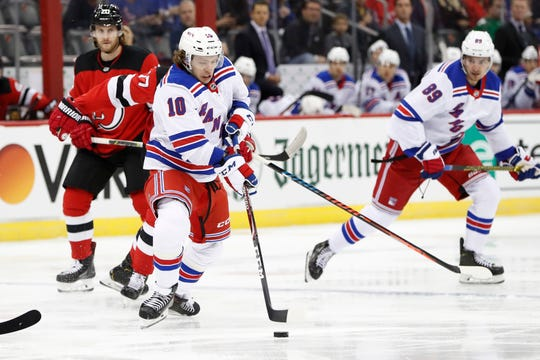 New York Rangers center Artemi Panarin (10) skates with the puck as he looks to pass with Rangers left wing Pavel Buchnevich (89) and New Jersey Devils' Blake Coleman watching during the first period NHL hockey game Thursday, Oct. 17, 2019, in Newark, N.J.