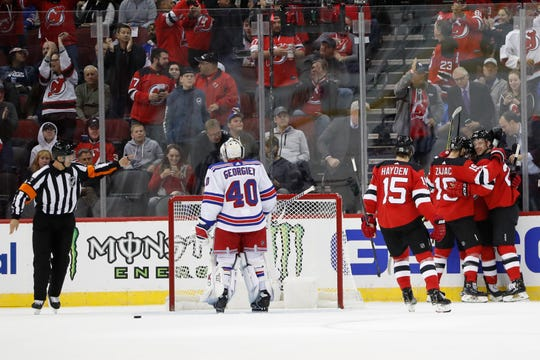 New Jersey Devils celebrate with center Blake Coleman, right, after he scored against New York Rangers goaltender Alexandar Georgiev (40) during the first period of an NHL hockey game Thursday, Oct. 17, 2019, in Newark, N.J.
