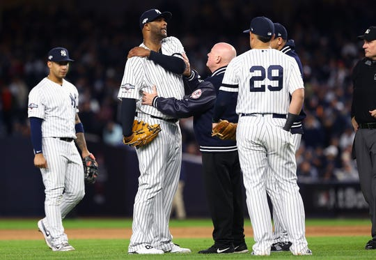 CC Sabathia #52 of the New York Yankees is assessed by the trainer before he comes out of the game against the Houston Astros during the eighth inning in game four of the American League Championship Series at Yankee Stadium on October 17, 2019 in New York City.