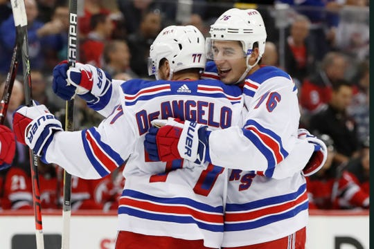 New York Rangers' Brady Skjei, right, embraces defenseman Tony DeAngelo (77), who scored a goal during the first period of an NHL hockey game against the New Jersey Devils on Thursday, Oct. 17, 2019, in Newark, N.J.