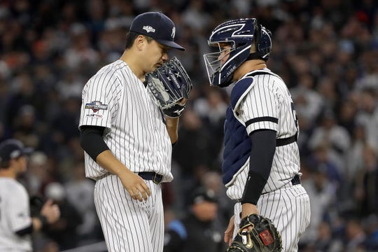 New York Yankees starting pitcher Masahiro Tanaka, left, meets with catcher Gary Sanchez on the mound after giving up a base hit to Houston Astros' Michael Brantley during the third inning of Game 4 of baseball's American League Championship Series, Thursday, Oct. 17, 2019, in New York. (AP Photo/Frank Franklin II)