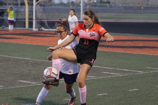 Aztec's Cara Daugherty controls the ball against Miyamura's Aja Francisco during Thursday's District 1-4A girls soccer match at Fred Cook Memorial Stadium in Aztec.