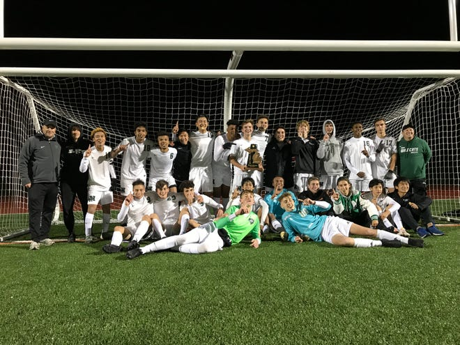 The Novi boys soccer team celebrates its district title after its 4-1 win against Birmingham Seaholm on Oct. 17.