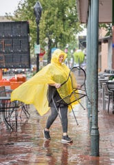 Timbre Bevak removes chairs and tables from in front of Four Seasons Market & Eatery in downtown Pensacola on Friday, Oct. 18, 2019.  They are preparing for a potential visit from Tropical Storm Nestor.