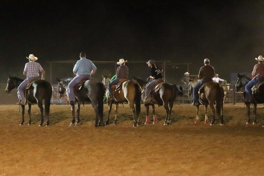 Denton, third from left, and his father, second from left, sit on their horses and chat with other competitors at a Friday evening jackpot competition on October 4, 2019 in Wickenburg.