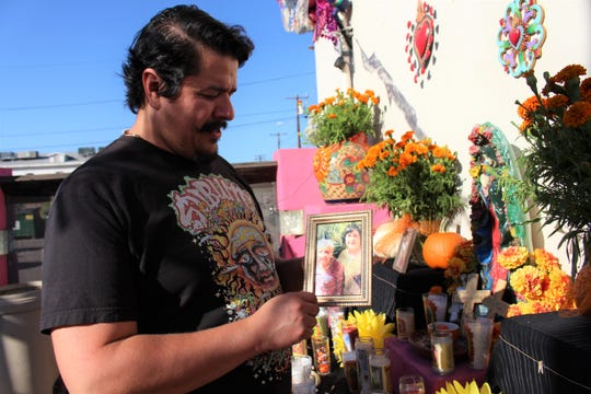 ET Rivera, owner of Tres Leches Cafe, holds up a photo of his great-grandmother (left) and grandmother, who is still alive, at the cafe's Dia de los Muertos community ofrenda on Oct. 17, 2019.