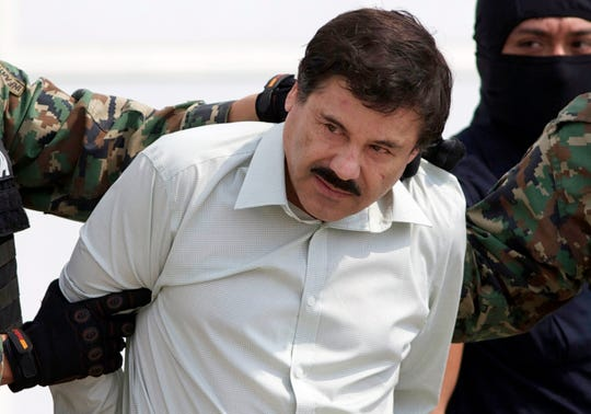 "In this Feb. 22, 2014 file photo, Joaquin ""El Chapo"" Guzman, the head of Mexico's Sinaloa Cartel, is escorted to a helicopter in Mexico City following his capture in the beach resort town of Mazatlan, Mexico. An intense gun battle with heavy weapons and burning vehicles blocking roads raged in the capital of Mexico's Sinaloa state Thursday, Oct. 17, 2019 after security forces located one of Guzman's sons who is wanted in the U.S. on drug trafficking charges. (AP Photo/Eduardo Verdugo, File)"