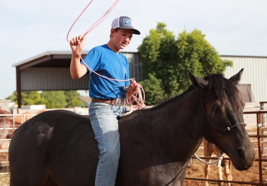 Denton practices swinging his rope while sitting bareback on Bubba, a two-year-old horse he trained himself, at his home in Waddell on October 16, 2019.