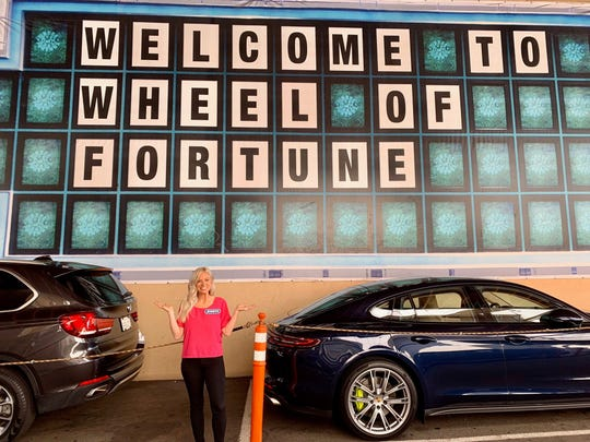 "Jennifer Hedrick of Algonac poses by a ""Wheel of Fortune"" wall."