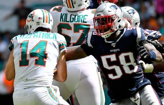 New England Patriots defensive end Keionta Davis (58) reaches for Miami Dolphins quarterback Ryan Fitzpatrick (14).