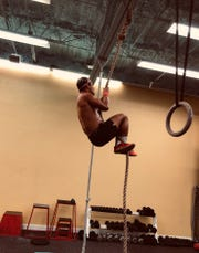 Rope climbing is one of the many exercise routines available through SWEAT.