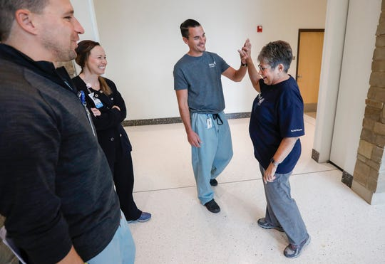 Trish Root high-fives physicians assistant Cody Giedd after having the nerves in her knee numbed with the Iovera device as Dr. Robert Jones and Registered Nurse Chandra Hazen smile at Mercy Orthopedic Hospital in Ozark, Mo., on Friday, Oct. 18, 2019.