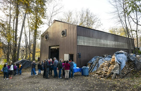 People gather around the Johanna Kiln for a lighting ceremony Friday, Oct. 17, at St. John's University in Collegeville. The kiln is the largest wood-fired kiln in North America.