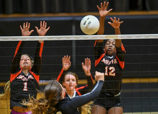Lincoln Park Academy's Aniya Patterson (12) blocks a shot from Katie Davis (foreground) of Alexander W. Dreyfoos School of the Arts and scores a point in the second game of the Girls District 12-4A Volleyball Championship at the Lincoln Park Academy gym on Thursday, Oct. 17, 2019, in Fort Pierce. Dreyfoos won the championship in the last moments of game five.