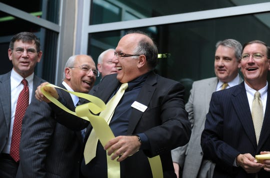 Rafick-Pierre Sekaly (center), co-director and chief scientific officer of the Vaccine & Gene Therapy Institute of Florida, plays with a segment of ribbon after the ribbon cutting ceremony marking their official opening while standing with (from left) Richard Houghten, of Torrey Pines Institute for Molecular Studies; Mel Rothberg, COO of VGTI; Larry Pelton; Joe Robertson (second from right), president of Oregon Health & Science University and Ken Pruitt, St. Lucie County property appraiser on Feb. 29, 2012. Nearly 300 guests attended the ceremony at the new $47 million, 100,000-square-foot research facility located in the Tradition Center for Innovation in Port St. Lucie.