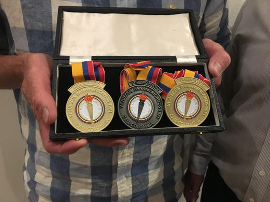 Jim McConica holds up replica medals to commemorate his swimming success at the 1971 Pan American Games. McConica's original medals were lost in the Thomas Fire, and friend and fellow swimmer Glenn Gruber researched and paid to make new ones.