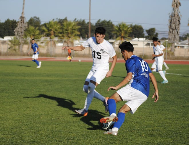 Oxnard College sophomore Erik Lopez takes on Moorpark defender JC Tamayo on Tuesday at the Condors' Nest. Oxnard handled Moorpark 5-0 in the WSC North opener for both teams.
