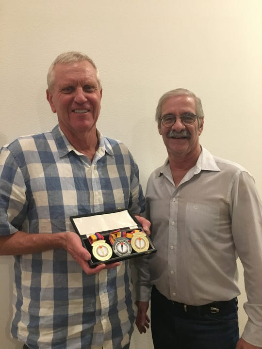 Jim McConica, left, holds up replica medals to commemorate his swimming success at the 1971 Pan-American games with friend and fellow swimmer Glenn Gruber. McConica's original medals were lost in the Thomas Fire, and Gruber researched and paid to make new ones.