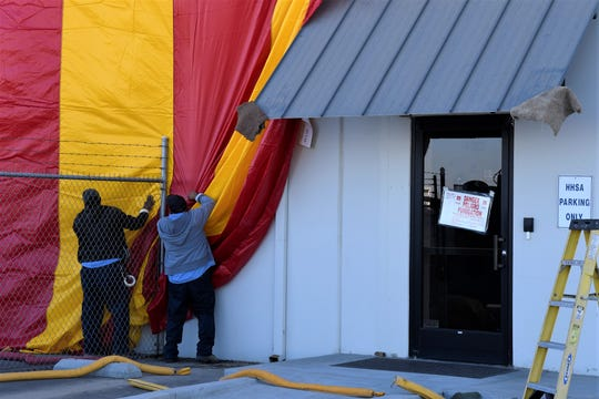 Workers prepare the Tulare County Department of Child Support Services Visalia office for fumigation on Friday, Oct. 18. The tenting follows a confirmed presence of bedbugs in the office's call center late last month.