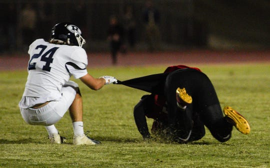 Redwood's Mitchell Wilson makes a tackle in the first half at a West Yosemite League high school football game between Redwood (7-0) and Hanford (7-0) in Hanford Thursday night.