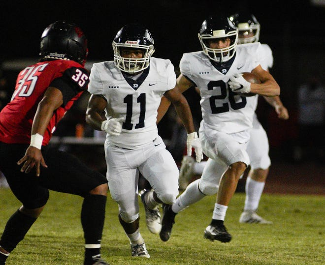 Redwood's James Richardson (11) leads the way for Redwood's Caden Shafer (26) during  a West Yosemite League high school football game between Redwood (7-0) and Hanford (7-0) in Hanford Thursday night.
