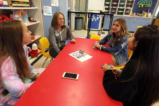 """Chef Jennifer Cook, second left, chats with junior Emily Ras, left, senior Jacqueline Canty and junior Valerie Lehner about designs for her next """"Foodie Bus"""" during an interior design class at Suffern High School Oct. 18, 2019. Cook converted a school bus into a restaurant on wheels and parks it in scenic locations for a unique dining experience. Now she has tasked interior design students to come up with a concept for a foodie bus targeting young adults."""