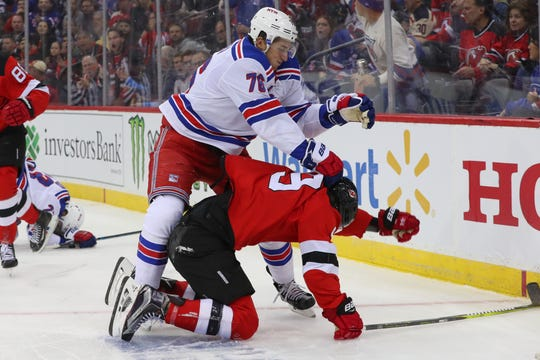 Oct 17, 2019; Newark, NJ, USA; New York Rangers defenseman Brady Skjei (76) knocks down New Jersey Devils left wing Taylor Hall (9) during the second period at Prudential Center.