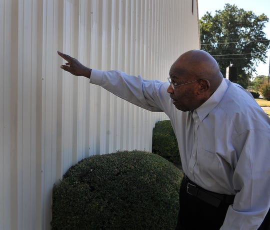 New Jerusalem Baptist Church pastor, the Rev. Angus Thompson, points out where vandalizes spray-painted graffiti on the back of the church located on Borton Street early last week.