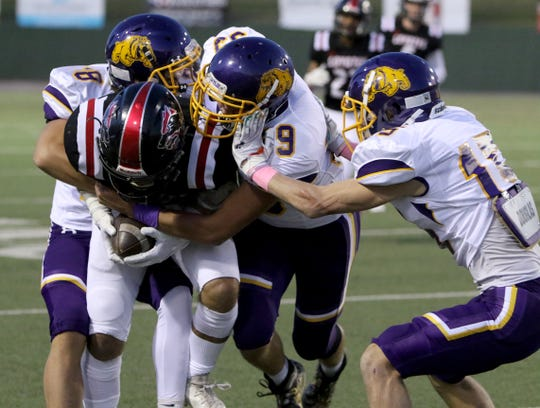 Wichita Falls High's Zach Williams is tackled by Abilene Wylie defenders Thursday, Oct. 17, 2019, at Memorial Stadium. The Bulldogs defeated the Coyotes 21-14 for their first win of the season.