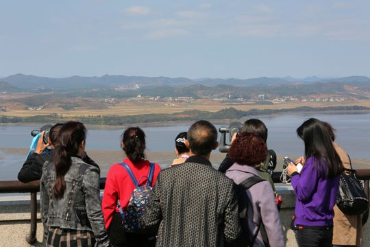 Visitors watch the North Korea side from the Unification Observation Post in Paju, South Korea, near the border with North Korea, Tuesday, Oct. 15, 2019. Amid swine fever scare that grips both Koreas, South Korea is deploying snipers, installing traps and flying drones along the rivals' tense border to kill wild boars that some experts say may have spread the animal disease from north to south.