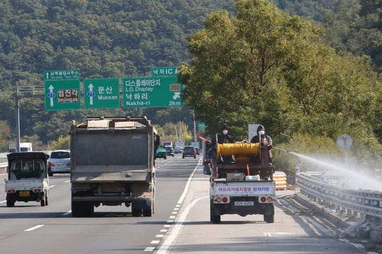 Disinfectant solution is sprayed from a vehicle as a precaution against African swine fever on the road in Paju, South Korea, near the border with North Korea, Tuesday, Oct. 15, 2019. Amid swine fever scare that grips both Koreas, South Korea is deploying snipers, installing traps and flying drones along the rivals' tense border to kill wild boars that some experts say may have spread the animal disease from north to south.